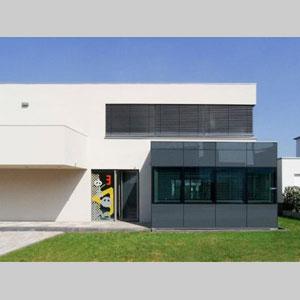 Die Scheibe wurde mit überdimensionalen Buchstaben des phönizischen Alphabets in leuchtenden Farben im Siebdruckverfahren bedruckt und bildet einen reizvollen Kontrast zur klaren puristischen Architektur des Hauses. Ausführung im Jahr 2009.